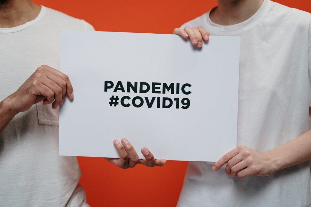 People Holding White Paper With Pandemic Covid19 Text